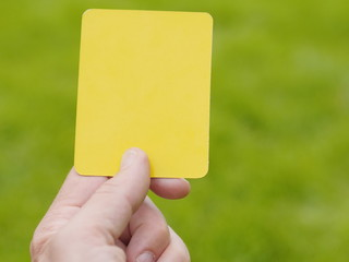 referee hand with yellow card