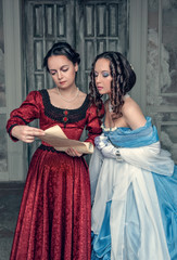 Beautiful girls in medieval dresses with scroll letter