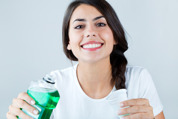 Beautiful girl using mouthwash. Isolated on white.