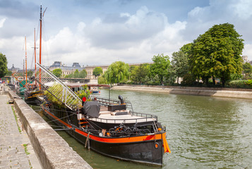 Old pleasure boats stand moored, Seine river coast in Paris, Fra