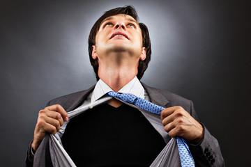 Business man tearing off his shirt