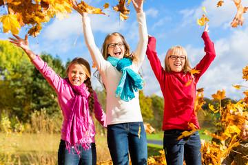 Freundinnen toben im Herbst Laub