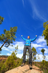 Hiking man reaching summit top cheering in forest
