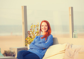 Redhead girl sitting in the cafe near sea coast.