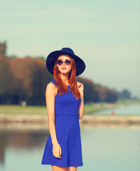 Redhead girl in sunglasses near lake in Versailles