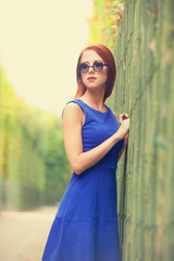 Redhead girl in sunglasses near fence in Versailles garden