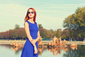 Redhead girl in sunglasses near lake in Versailles