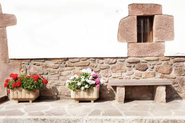 banco de piedra  con maletones de geranios