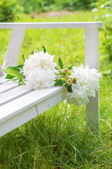 Beautiful bouquet of white peonies on a white wooden bench