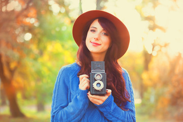 Brunette girl with camera in the park in sunset time