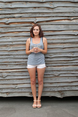 Stylish young girl standing on a wooden wall background.