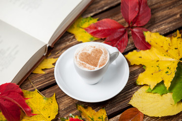 Autumn leafs, book and coffee cup on wooden table.
