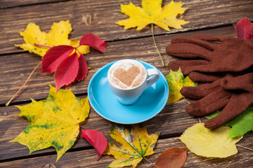Autumn leafs,gloves and coffee cup on wooden table.