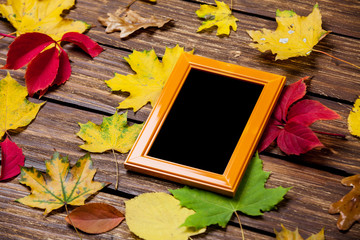 Autumn leafs and frame for photo on wooden table.