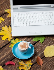 Autumn leafs, notebook and coffee cup on wooden table.