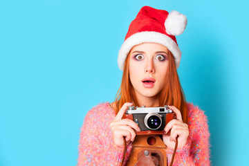 Redhead girl in hat and camera on yellow background.