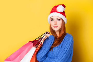 Redhead girl with shopping bags on yellow  background.