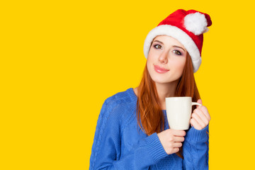 Redhead girl with cup on yellow background.