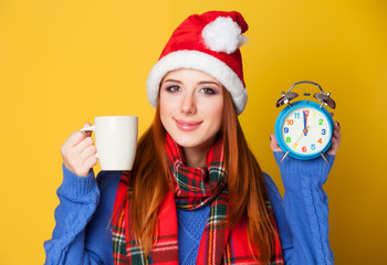 Redhead girl with cup and clock on yellow background.