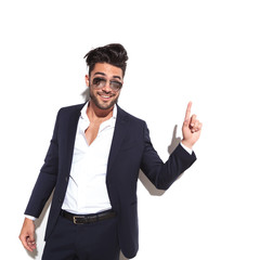 business man wearing sunglasses smiling and pointing up
