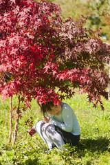 Девочка прячится под листвой дерева