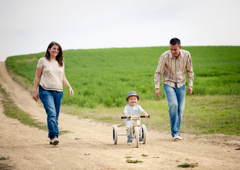 Family with little boy on tricycle in nature