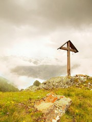 Wooden cross at a mountain top in the alp. Cross on peak of hill