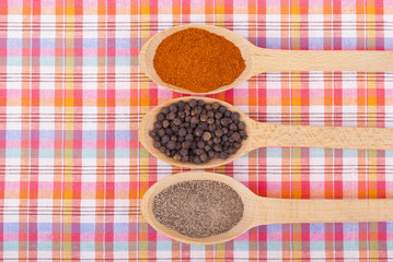 Whole and ground pepper in a wooden spoon on the tablecloth.