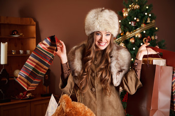 Pretty woman holding Christmas gifts after shopping