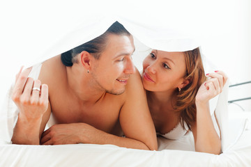 guy and woman  together under sheet on bed