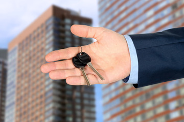 Cropped image of estate agent giving house keys in office