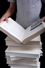 Enfant lisant un livre ouvert sur pile de livres blancs