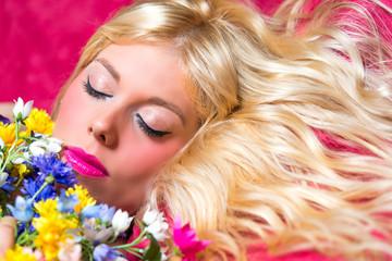 Blonde Frau mit blauen Augen und Blumen