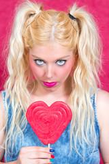 Blonde Frau mit blauen Augen und Herz in der Hand