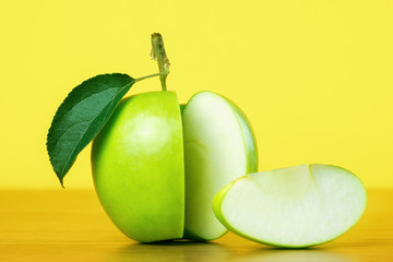 Green apple with slice on yellow background