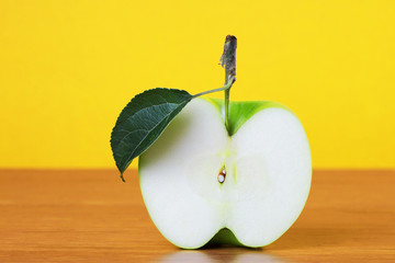 Green apple slice with leaf against yellow background