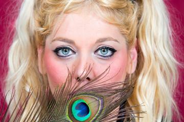 Blonde Frau verdeckt ihr Auge mit Pfauenfeder