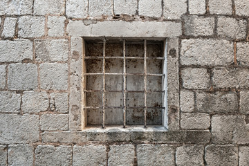 Locked ancient stone prison wall with metal window bars