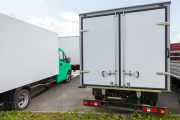 Rear view of new standing white cargo trucks