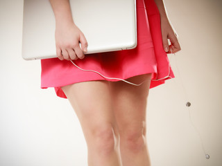 Female legs and laptop with headphones