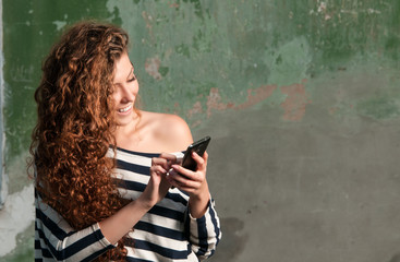 Young smiling woman using smartphone