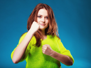 teen girl clenching fists on blue