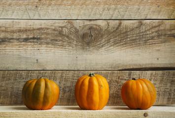 Three Pumpkins on Old  Wooden Background