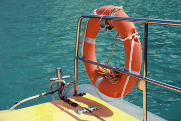 Red lifebuoy hanging on railings of safety rescue boat