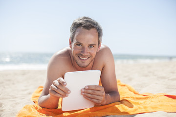 handsome man on the seaside lying on a beach towel to use a digi