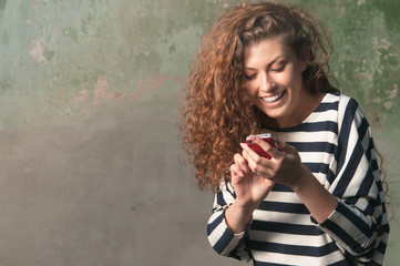 Young smiling woman texting on smartphone