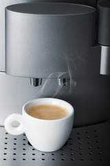 Small cup of hot espresso in modern automatic coffee machine