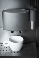 White ceramic cup stands in modern coffee machine