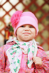 Funny smiling Caucasian baby girl in pink, closeup outdoor portr