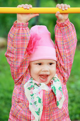 Funny smiling Caucasian baby girl in pink, outdoor portrait